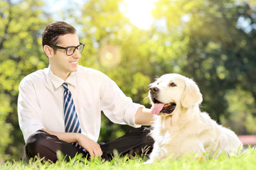 Young man sitting on a green grass next to a dog in a park on a