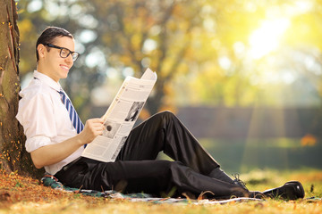 Young man with tie sitting on a grass and reading a newspaper