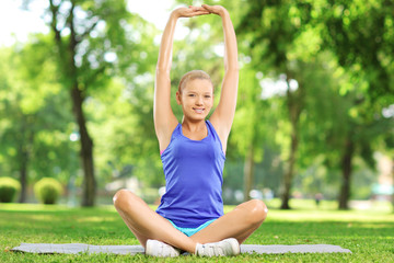Young woman exercising in park on sunny day