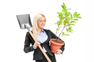 Young woman holding a shovel and a plant
