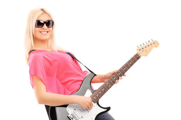 Young woman playing on electric guitar