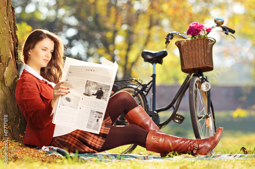 Young woman with bicycle sitting on a green grass and reading a