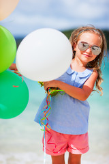Adorable little girl with balloons at beach