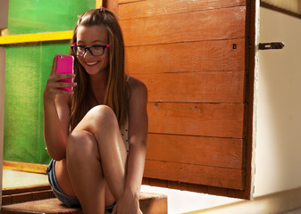 Teenage girl sitting in front of wooden house, with cellphone