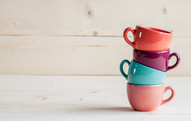 Colorful coffee cups over wooden background
