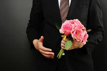 ピンクの花束を持っているスーツのビジネスマン