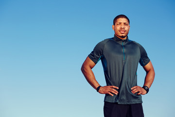 African American runner standing on blue sky background