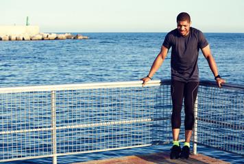 Sporty athletic runner doing pull-ups lying on pier railing