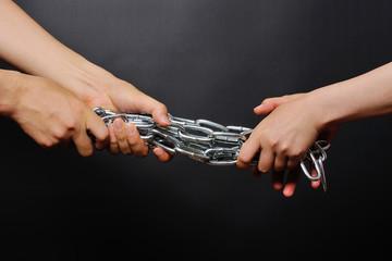 鎖を引き合う二人の人間の手