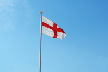 The English flag flies against a blue sky
