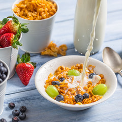 Cornflakes with fruits flooded with milk