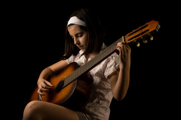 Teenage girl playing a guitar