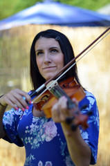 Woman plays violin during outdoor summer event