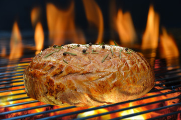 Grilled meat on the grill with flames