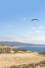 Paragliding over the clifftop rocky coast