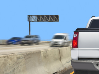 White pickup truck stopped on freeway near concrete barrier