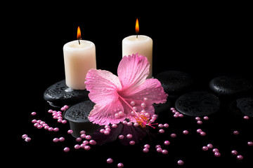 Beautiful spa still life of pink hibiscus, candles, zen stones w