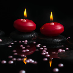 Beautiful spa concept of candles, zen stones with drops and pear