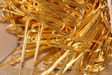 small heap of gold paper clips serve to compound documents