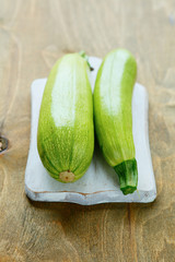 Two green zucchini on a board