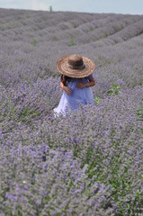 Little girl with straw hat in a lavander field