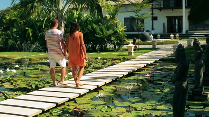 Couple walking on pond in exotic garden and holding hands