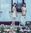 Tow women in dress near luxury building facade among roses