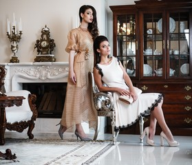Two young women near fireplace in luxury house interior