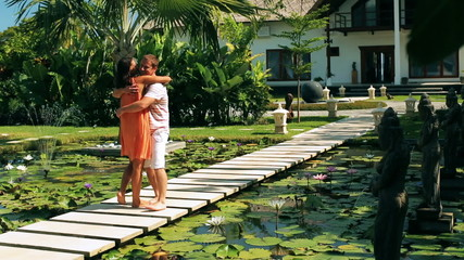 Happy couple meeting on pond in exotic garden and kissing