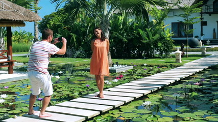 Man taking photo of his girlfriend in exotic garden