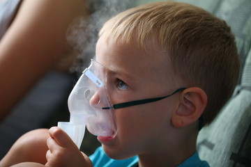 boy makes inhalation from cough and runny nose at home