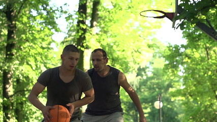 Two man playing basketball in park court, super slow motion