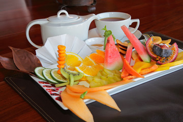Breakfast platter of fresh fruit and a pot of tea