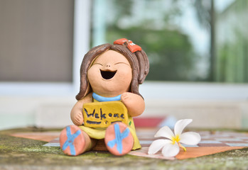 Welcome sign stone doll with white flower on the table