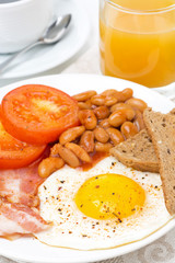 English breakfast with fried eggs, bacon, beans, toasts