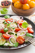 Greek salad with feta cheese on a plate, vertical