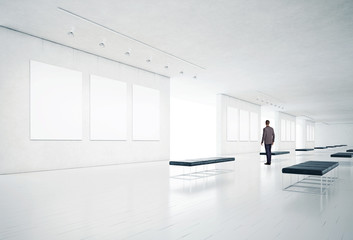 gallery room and man looking at empty frames