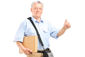 Mature courier holding a package and giving thumb up