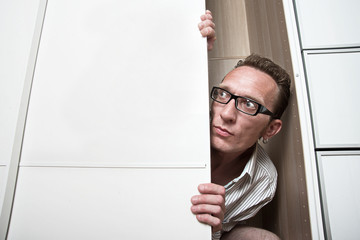 Frightened man peep out white wardrobe  Copy space left