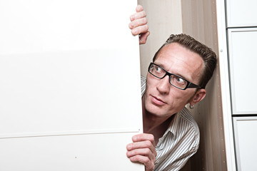Surprised man inside white wardrobe  Copy space left