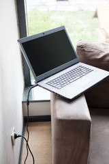 laptop on sofa handrail