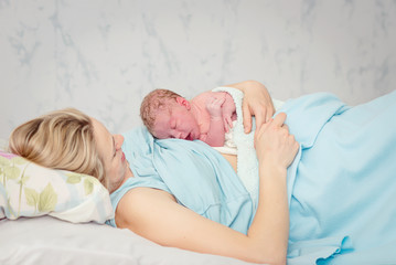 Young beautiful woman with a newborn baby after birth