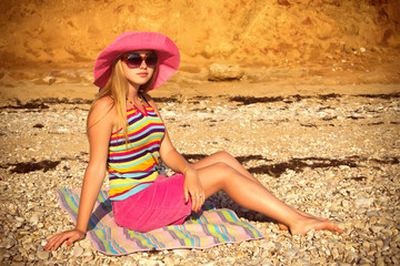 Girl on the beach in a pink hat.