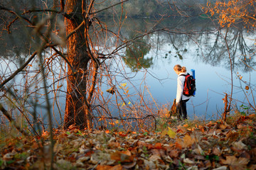 Woman traveler near forest river in autumn