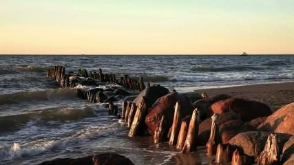 Wellen und Buhnen bei Sonnenuntergang