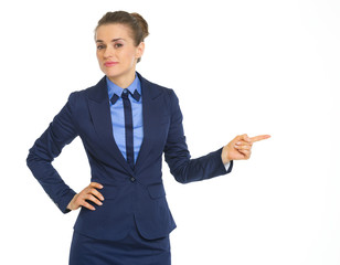 Portrait of doubting business woman pointing on copy space
