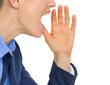 Closeup on business woman shouting through megaphone shaped hand