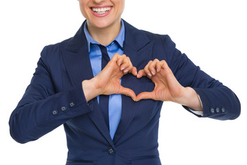 Closeup on happy business woman showing heart with fingers