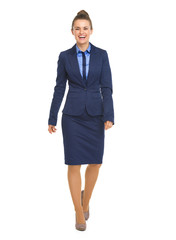 Full length portrait of smiling business woman going straight