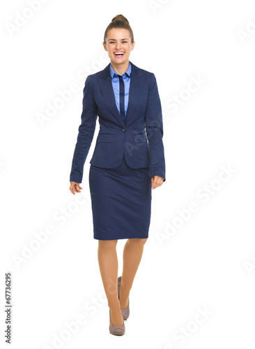 canvas print picture Full length portrait of smiling business woman going straight